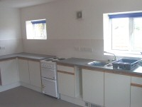 Fitted kitchen with electric cooker and fridge.